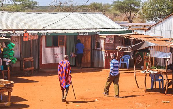 Обычный придорожный поселок и масай в традиционной одежде