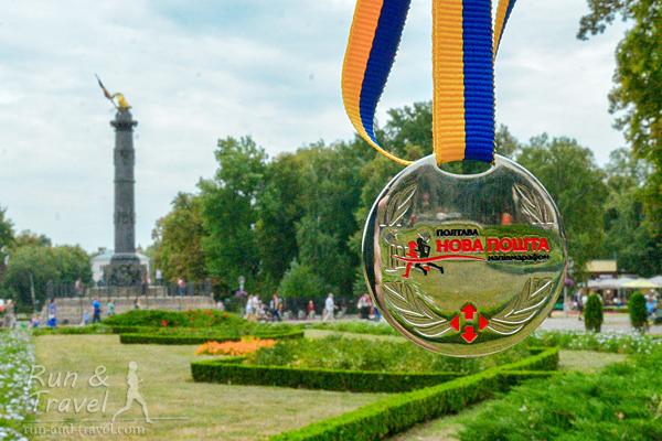 Медаль и Корпусный сад на фоне. Надпись с названием спонсора могла бы быть поменьше, а с названием мероприятия – побольше.